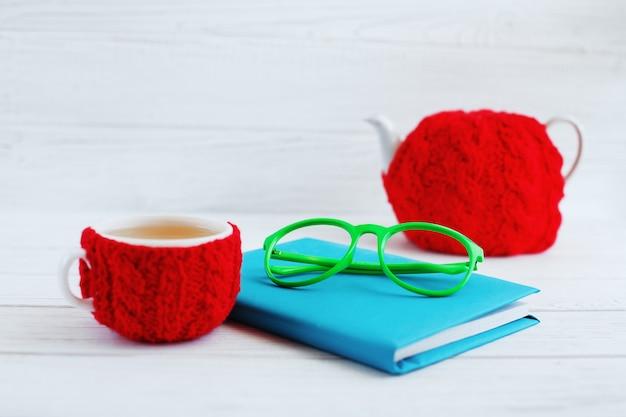 O livro, copos, uma xícara de chá e bule