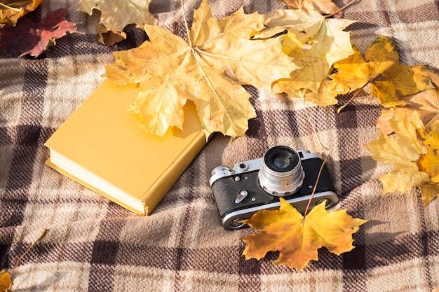 O livro e a câmera retros colocam em uma manta quadriculada marrom com as folhas de outono amarelas. conceito da queda e recreação ao ar livre. vista plana, vista superior