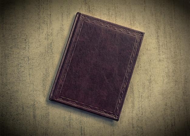 O livro é roxo escuro sobre um fundo cinza grunge, vista superior. foto matizada com vinheta, imagem tonificada retro
