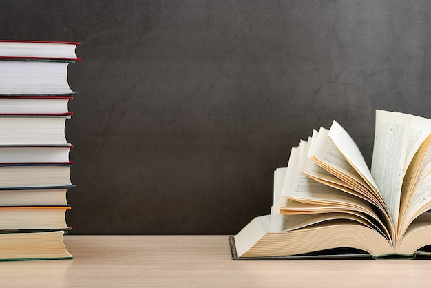 O livro está aberto, as folhas são em forma de leque em um fundo preto ao lado de uma pilha de livros.