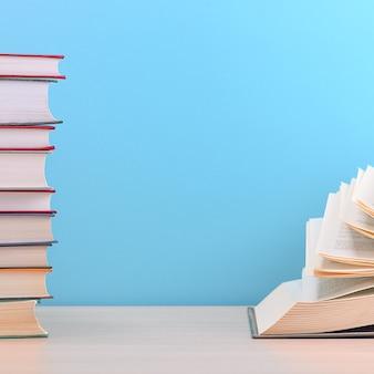 O livro está aberto, as folhas são em forma de leque sobre um fundo azul ao lado de uma pilha de livros.