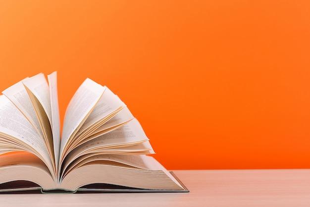 O livro está aberto, deitado sobre a mesa, com folhas espalhadas em um fundo laranja.