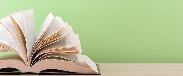 O livro está aberto, deitado sobre a mesa, com folhas espalhadas sobre um fundo verde.
