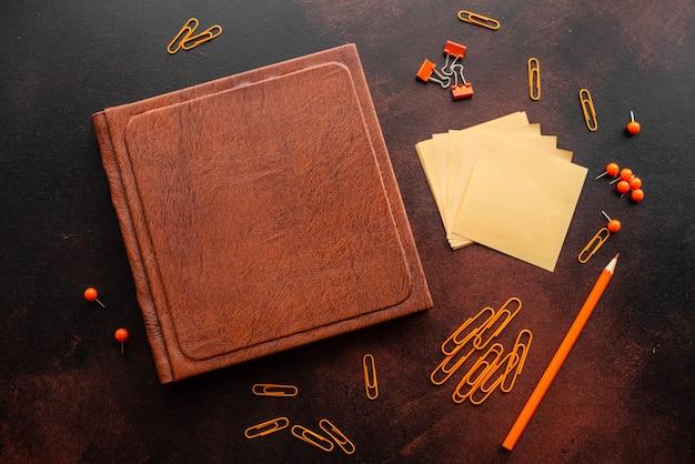 O livro, lápis, clipes de papel e folhas para marcas encontram-se em um desktop