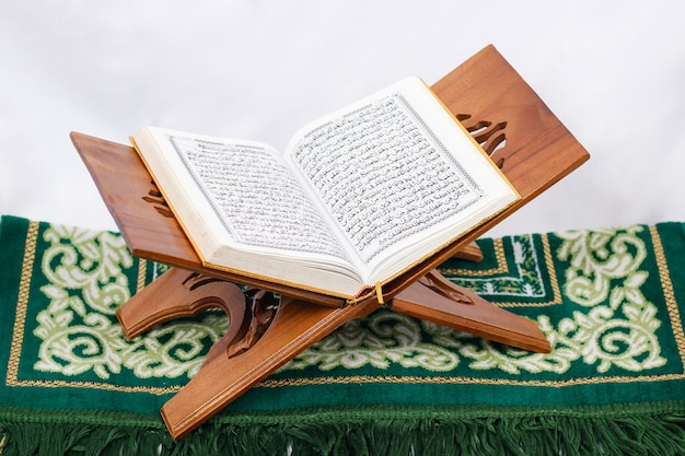 O livro sagrado al quran e tapete de oração isolado no fundo branco
