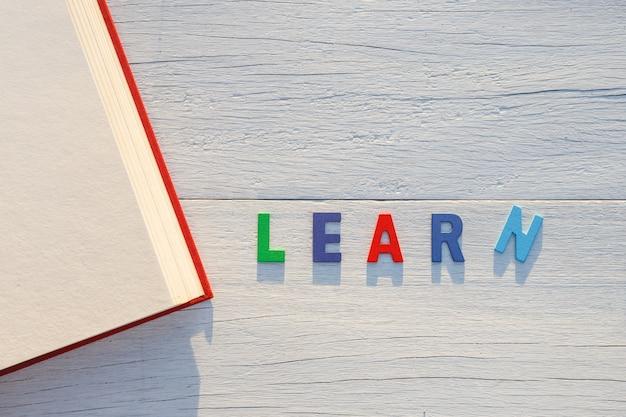 O livro velho e aprenda a palavra colorida do alfabeto. vista superior em fundo branco de madeira