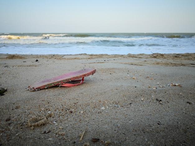 O lixo cor-de-rosa do deslizador lava acima na praia.