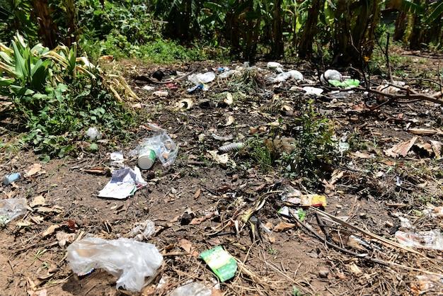 O lixo no lixo derramado parque na terra da cidade grande usou a poluição ambiental suja das garrafas plásticas sujas.