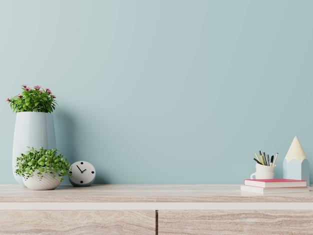 O local de trabalho moderno com mesa criativa com plantas tem parede azul.