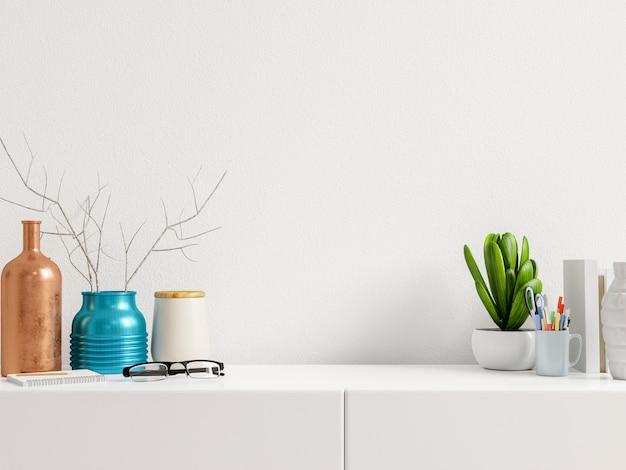 O local de trabalho moderno com mesa criativa com plantas tem parede branca.