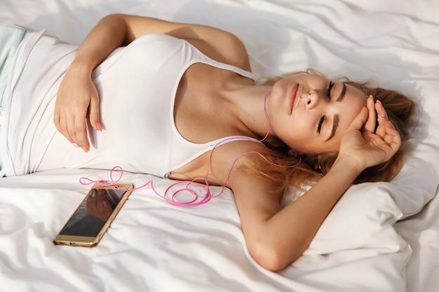 O loiro dormindo escuta a música que está deitada na cama