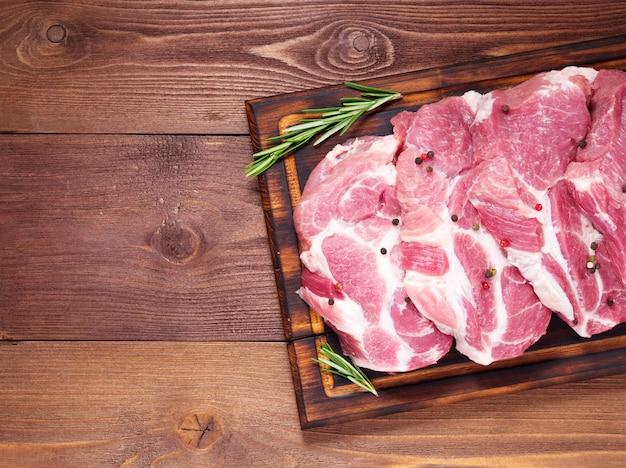 O lombo de carne de porco cru desbasta na placa de corte no fundo de madeira escuro, vista superior, espaço da cópia.