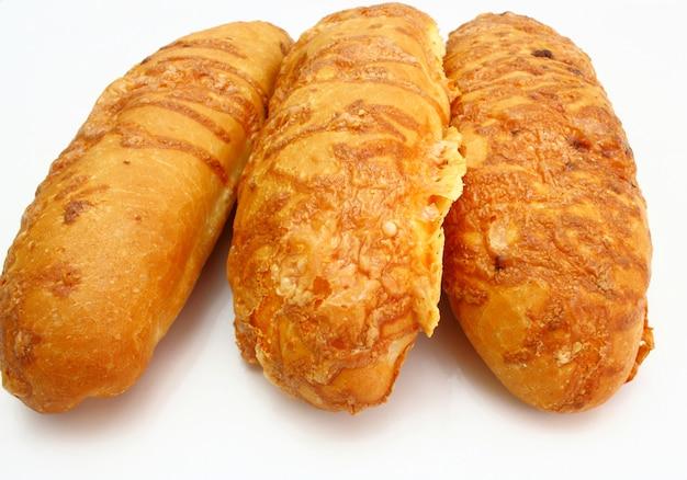 O longo pão corado é espalhado pelo queijo isolado