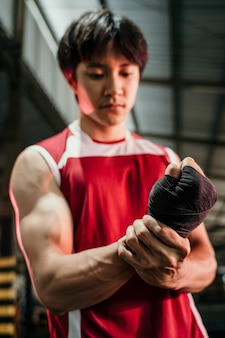 O lutador asiático final se preparando, lutador asiático musculoso usando pulseira preta no pulso