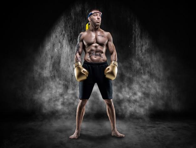 O lutador profissional está parado na fumaça em um lugar escuro. artes marciais mistas, muay thai, conceito de kickboxing. mídia mista
