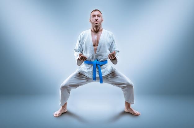 O lutador profissional usa um quimono. ele está se preparando para demonstrar o kata. o conceito de artes marciais mistas, caratê, sambo, judô, jiu-jitsu. mídia mista