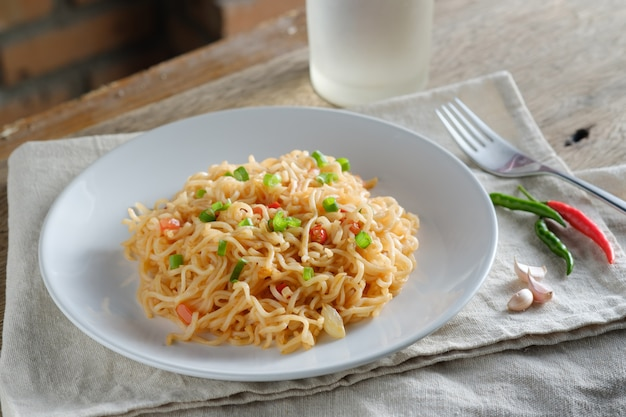 O macarrão está em um prato branco redondo, colocado sobre uma mesa de madeira. conceito de macarrão com espaço de cópia