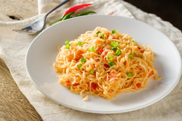 O macarrão está em um prato branco redondo, colocado sobre uma mesa de madeira. conceito de macarrão