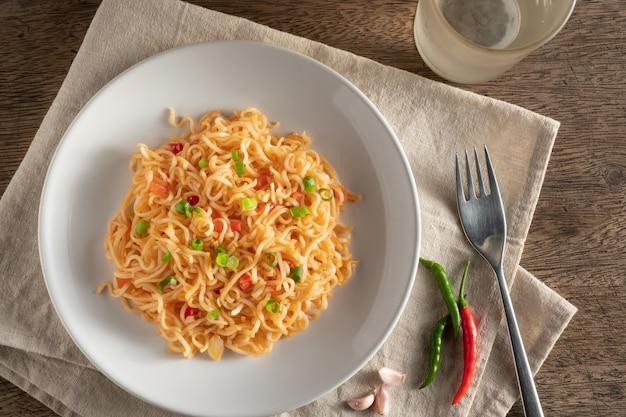 O macarrão está em um prato branco redondo, colocado sobre uma mesa de madeira. macarrão com copysapce