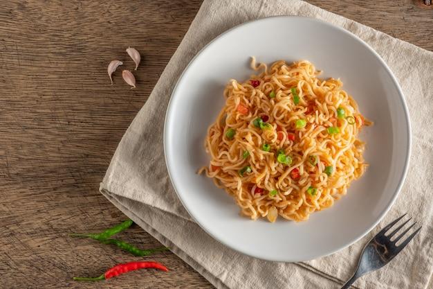 O macarrão está em um prato branco redondo, colocado sobre uma mesa de madeira.