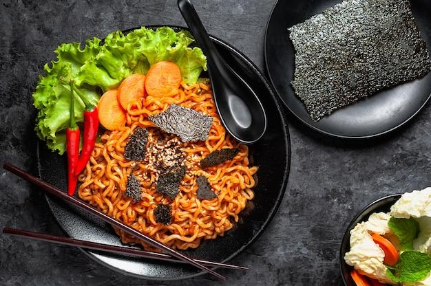 O macarrão instantâneo picante coreano quente dos ramen do sabor da galinha, agita o macarronete fritado.