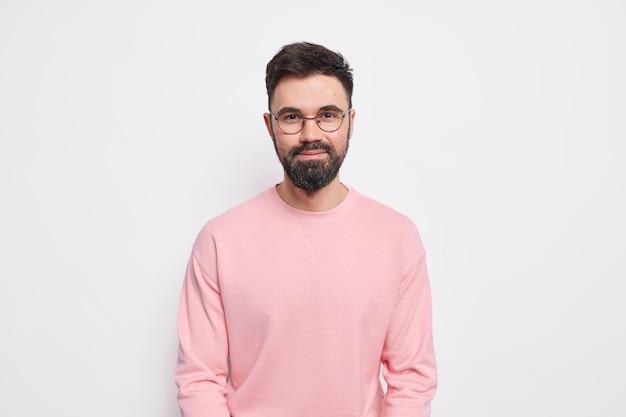 O macho barbudo confiante parece satisfeito, tem um sorriso amável e amigável no rosto e usa óculos redondos e macacão rosa