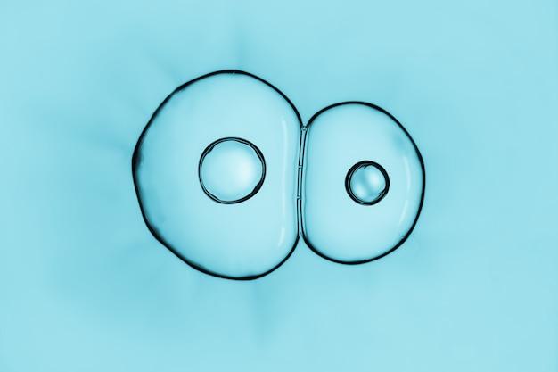 O macro próximo acima de bolhas de sabão olha como a imagem científica do processo de divisão das pilhas.