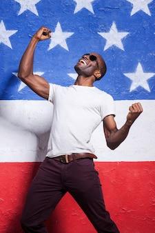 O mais feliz do mundo! africano jovem feliz em óculos de sol, levantando os braços e sorrindo enquanto se apoiava na bandeira americana