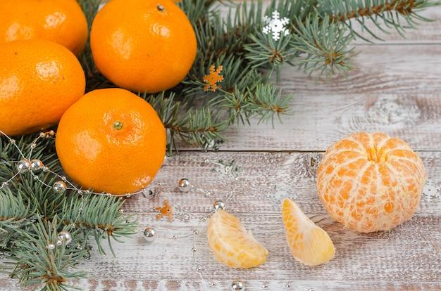O mandarino descascado em um fundo de madeira com filiais do abeto vermelho. ano novo e fundo de natal.