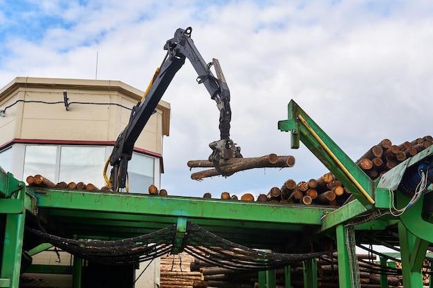 O manipulador hidráulico controlado controla a posição das toras na esteira de alimentação em uma serraria moderna