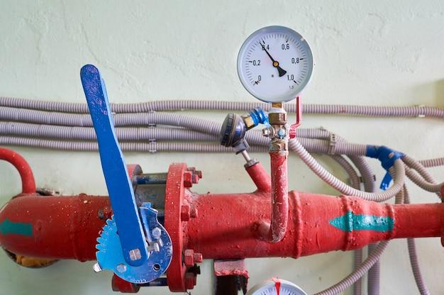 O manômetro indica a pressão da linha tingida de vermelho com válvula azul.
