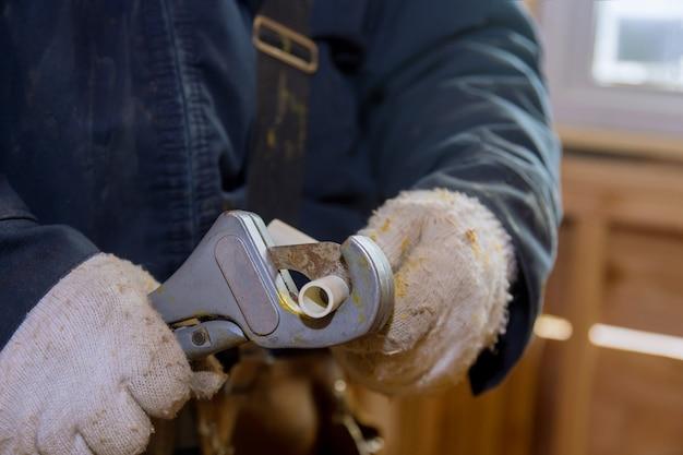 O manual do homem corta um pedaço de canos de polipropileno para a instalação da linha de água de uma nova casa em construção