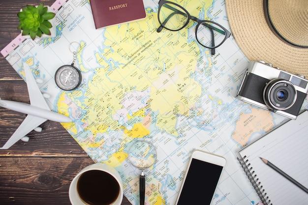 O mapa na velha mesa de madeira com acessórios turísticos na vista superior, plana leigos