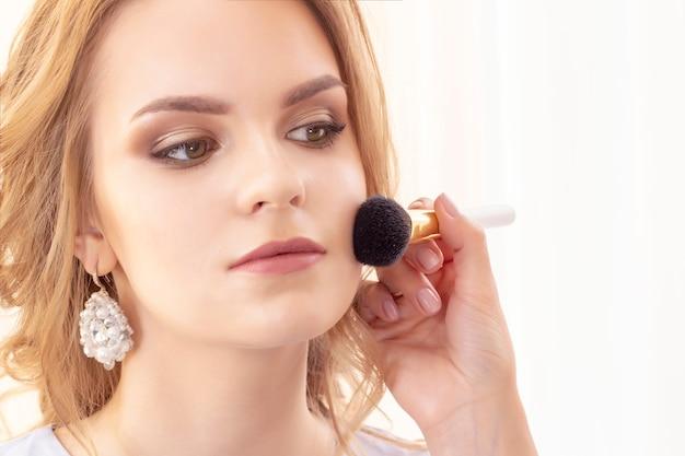 O maquiador aplica um belo pó de modelo e blush com um pincel grande no rosto