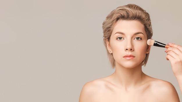 O maquiador aplica uma base tonal em pincel plano no rosto de uma bela modelo