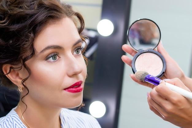 O maquiador aplica uma leve camada de pó fosco usando um pincel de maquiagem profissional. menina maquiadora
