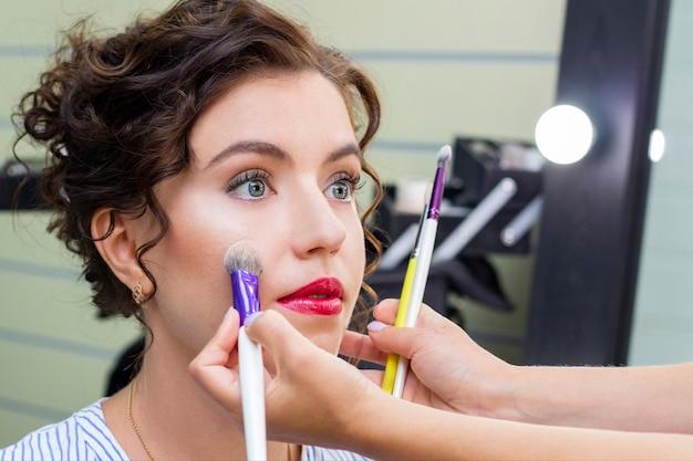O maquiador aplica uma leve camada de pó fosco usando um pincel de maquiagem profissional.