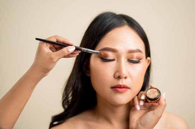 O maquiador aplicou sombra no rosto de uma linda mulher asiática. Foto Premium