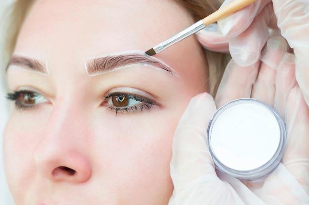 O maquiador faz marcações com lápis branco para as sobrancelhas e pinta as sobrancelhas. maquilhagem profissional e cuidados faciais.