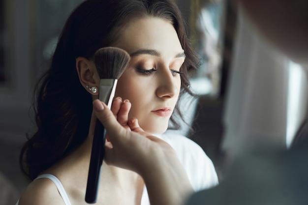 O maquiador maquia uma linda mulher pela manhã. beleza natural