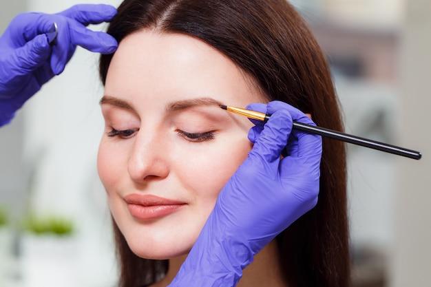 O maquiador pinta as sobrancelhas para o cliente