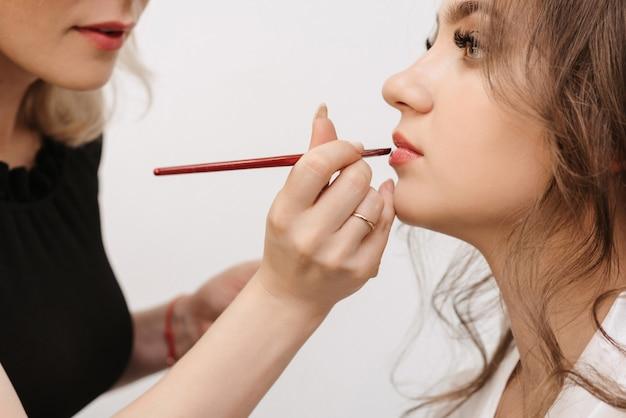 O maquiador pinta os lábios de uma noiva caucasiana com um pincel labial em um salão de beleza profissional