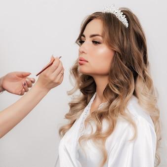 O maquiador pinta os lábios de uma noiva com um pincel labial em um salão de beleza profissional