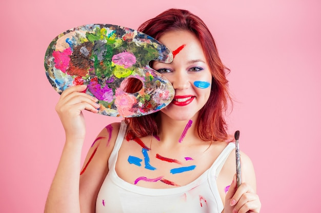 O maquiador visagiste sujo mancha de tinta na paleta do rosto nas mãos em um fundo rosa no estúdio.