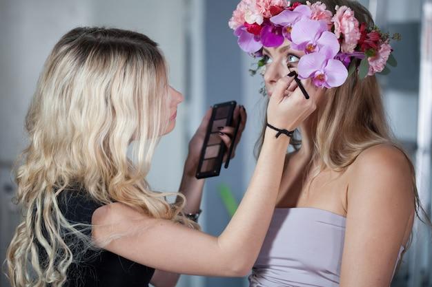 O maquilhador da jovem mulher faz a composição, menina do olho da pintura.