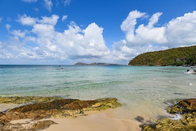 O mar acena na água da praia da areia e na costa rochosa do seascape da costa. vista da bela paisagem tropical praia mar ilha com oceano azul céu e resort fundo nas férias de verão tailândia praia