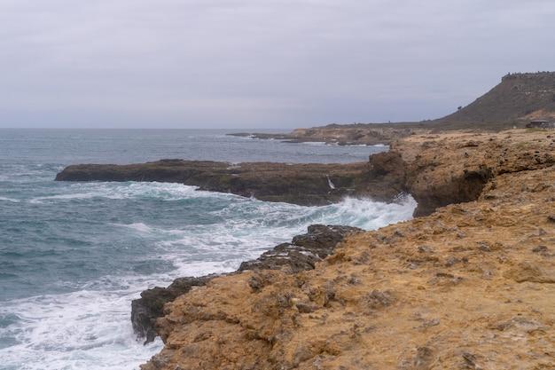 O mar batendo contra as rochas na chocolatera em salinas, equador