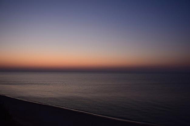 O mar calmo antes do amanhecer é fotografado à distância de um ângulo alto. abaixo está uma praia vazia