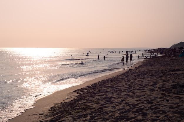 O mar cintilante ao pôr do sol com silhuetas de pessoas descansando. viagem e turismo.