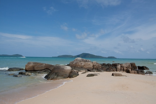 O mar com praias de areia branca e rochas tem um céu com nuvens brancas.